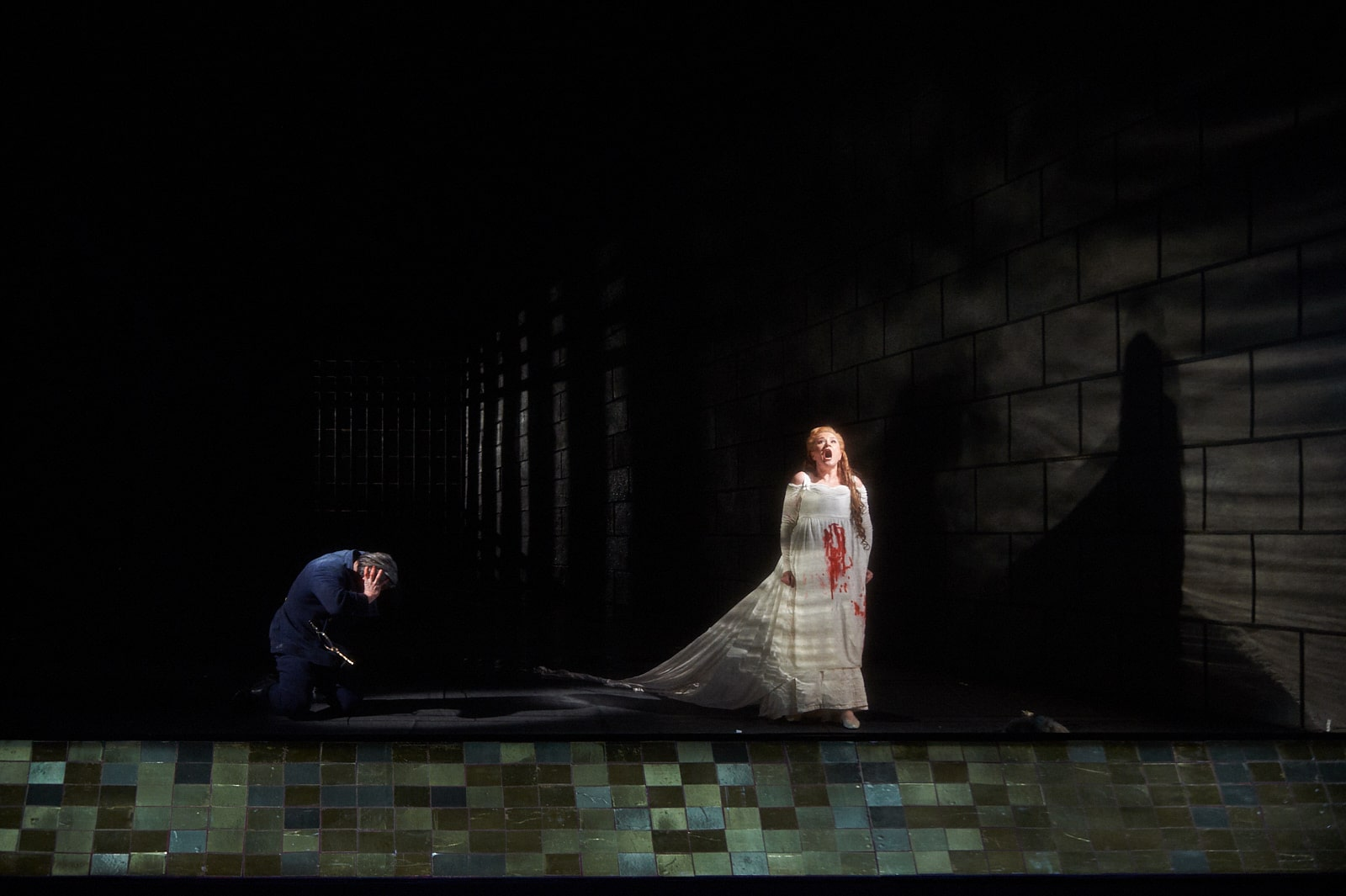 Blue-uniformed man cringes as bride in blood-stained gown sings against water-reflected light in front of blue-tiled path.