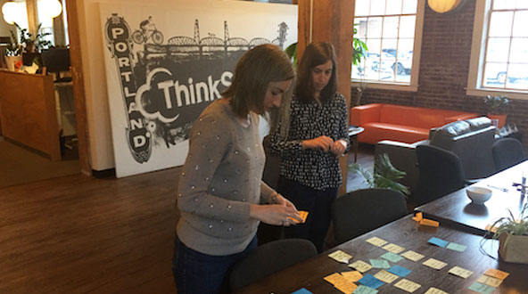 Two women sorting through features with post-it notes