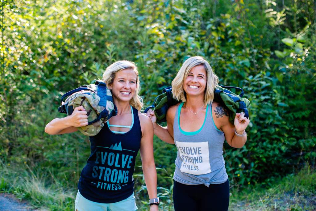 EVOLVE Strong Fitness coaches outside with workout sandbags