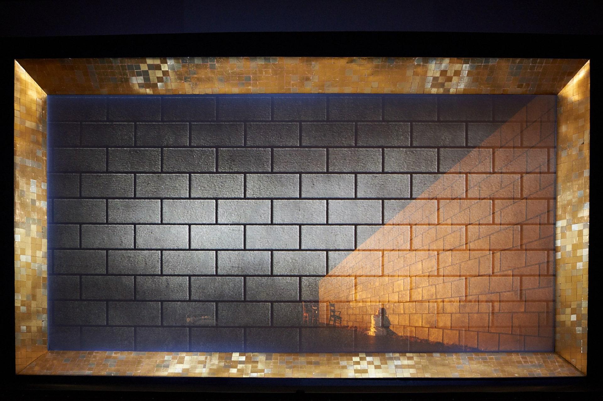 Gold tiles frame transparent brick scrim, revealing angled brick wall behind.