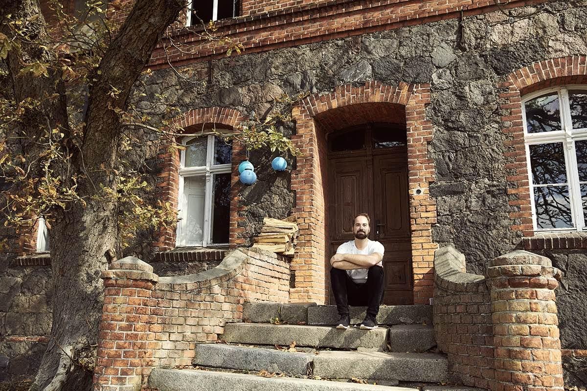 Ein Mann der in einem Hauseingang sitzt