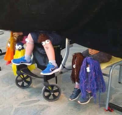 Παιδιά κάθονται με ψεύτικα μάτια και μαλλιά κολλημένα στα γόνατα.
