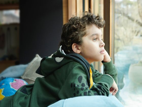 Boy gazing wondrously out his bedroom window