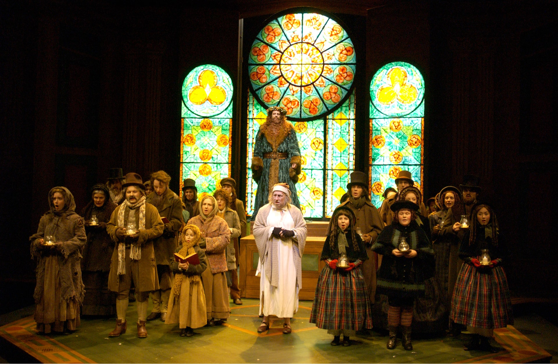 Man in nightclothes stands among Victorian carollers, watched Father Christmas in front of stained-glass window.