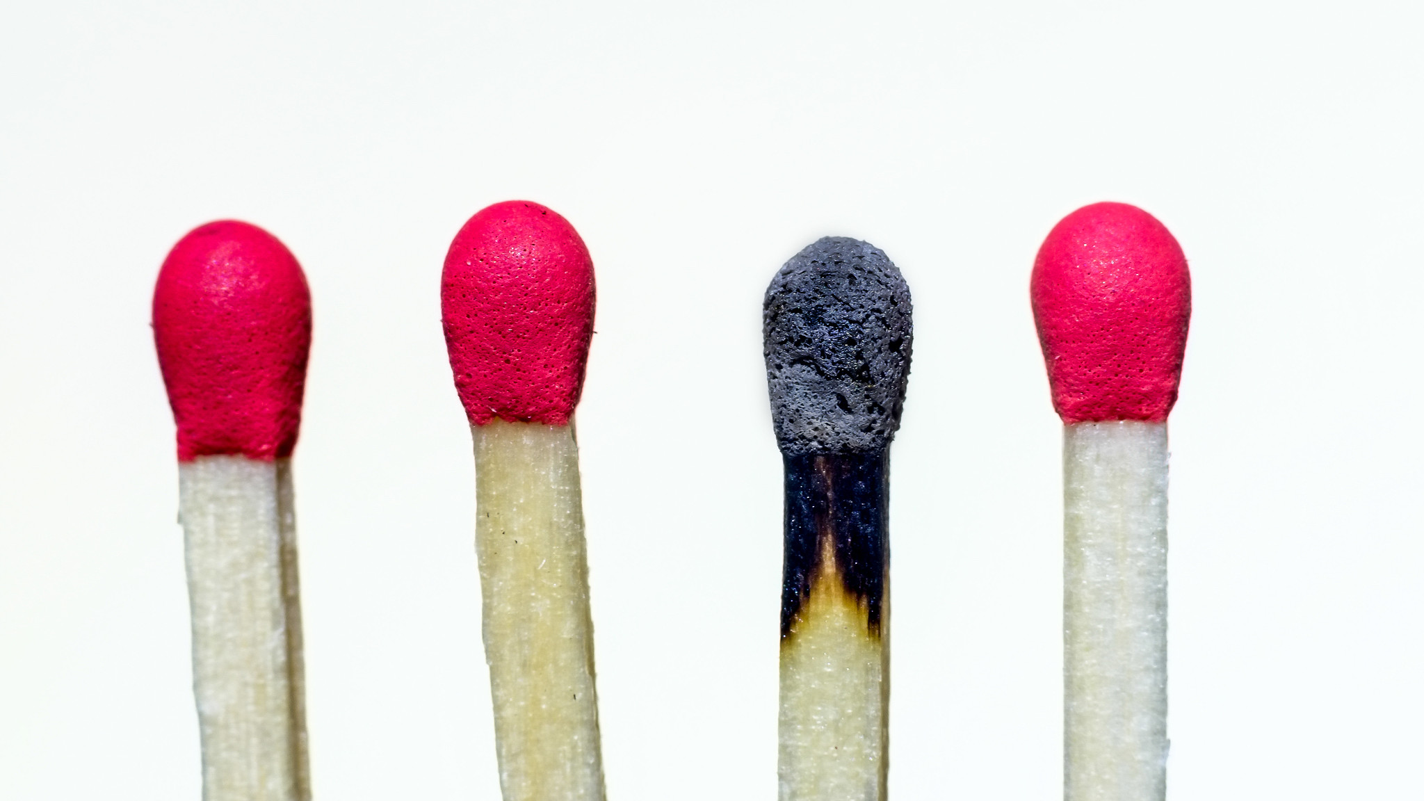 Image of 4 matches against a white background. One of the matches is already burnt.
