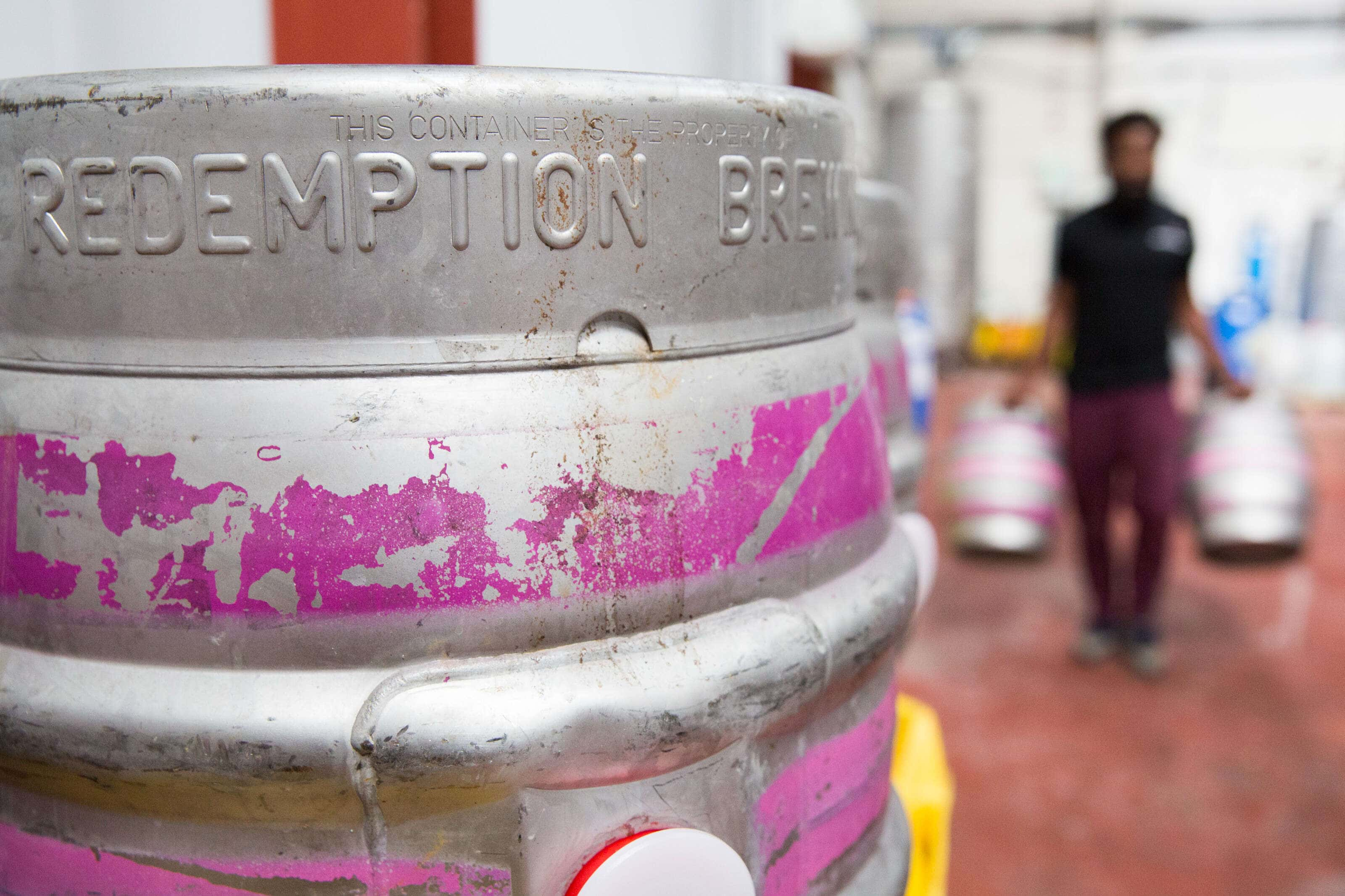 Redemption Brewery cask with a person carryinng two casks in the backgroun