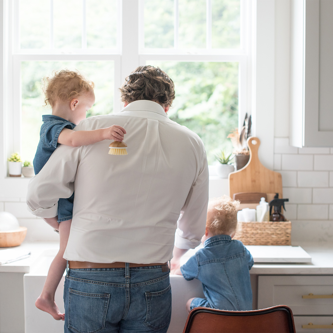 Man with his back to the camera stands over a kitchen sink with two young boys