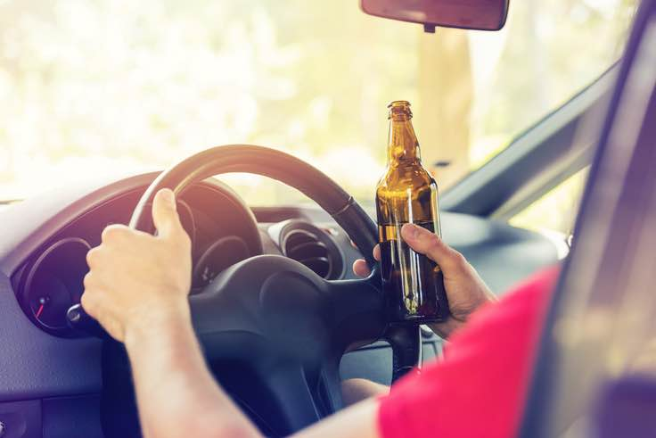 Close-up of hands on steering wheel with beer in hand