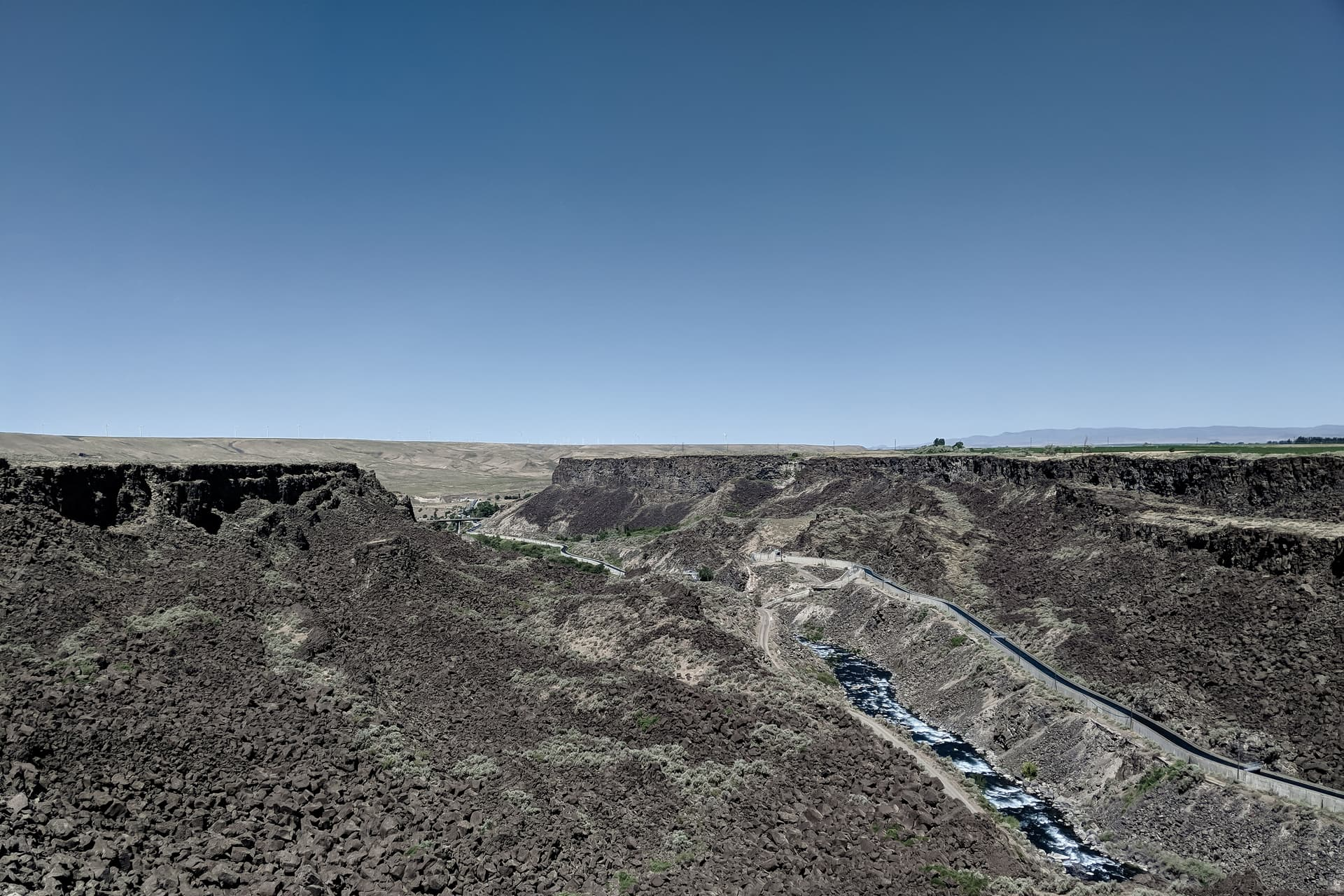 A river cuts a deep, sheer canyon through the basalt underlying otherwise empty desert scrubland. To the right of the river is a raised concrete irrigation canal.