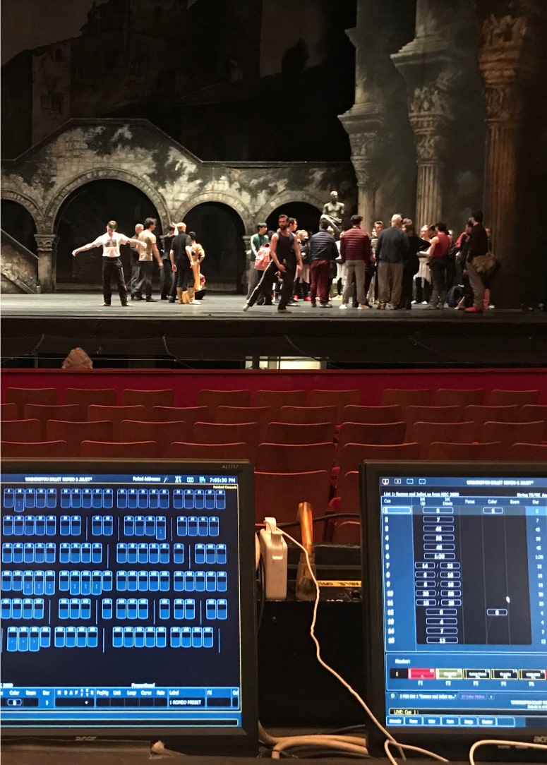 Two active computer monitors at production desk, with dancers rehearsing onstage in the background.
