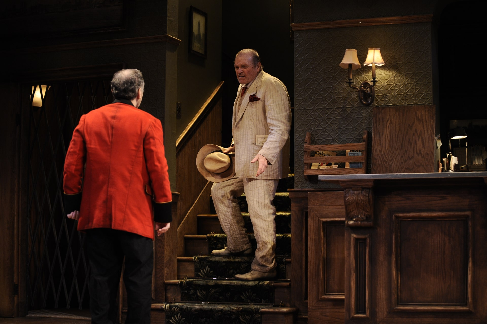 Dishevelled burly man in summer suit stands partway up hotel lobby stairs, speaking with red-suited desk clerk.