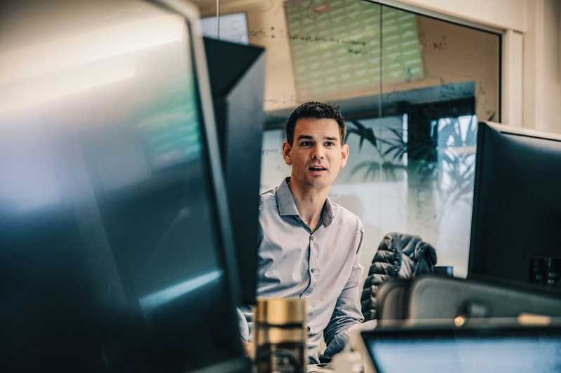 Dekorativt bilde at kontor med flere skjermer. Man kan se en mann som sitter foran en skjerm.