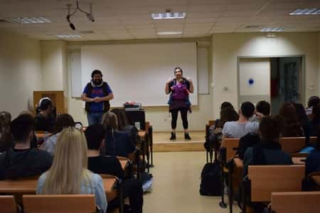 Aleksandros and Aggeliki giving an educational presentation to a group of students, while also holding their baby.