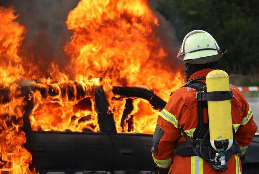 Car on fire, firefighter