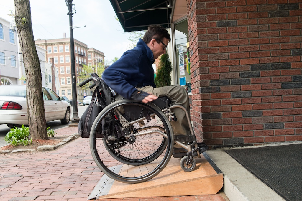 A wheelchair user utilizes my same ramp design for access at a single-step  entrance in Boston.