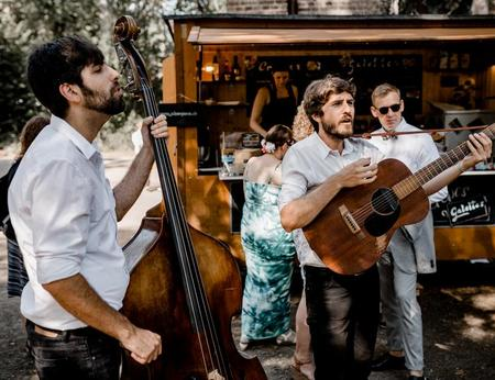 Zwei Musikanten machen Live Musik bei einer Hochzeit vor einem schönen Crêpestand mit Holzoptik