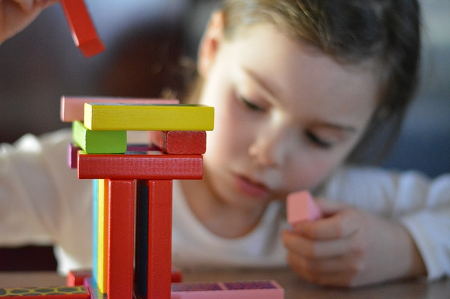 Child Playing with Wooden Math Manipulatives