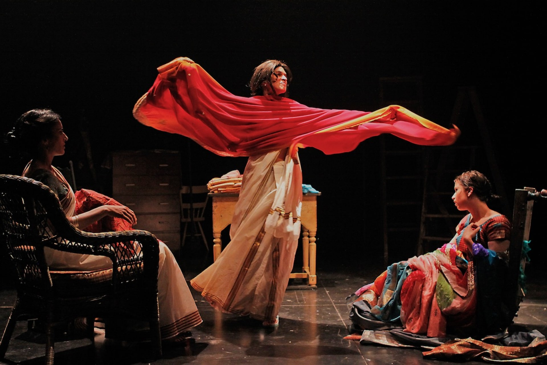 Woman dances with red fabric between two seated women.