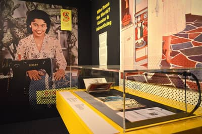 A wall titled 'Who Runs the World? Gender & Advertising'. Some magazines and a picture are in a showcase. Behind the showcase, a giant ad on the wall featuring a cheerful woman with her Singer sewing machine is featured.
