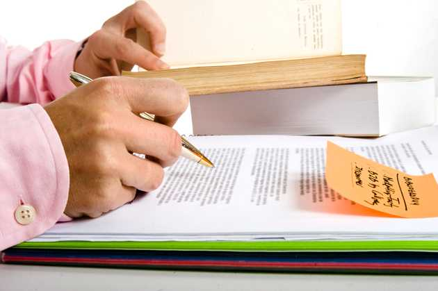 Man with pen reviewing paper