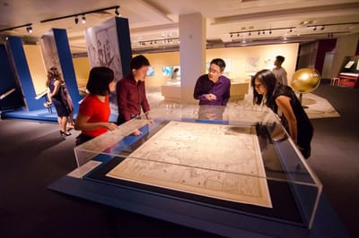 A table showcase with a map is surrounded by a curator and his tour group. Some of them are looking at the map, while the others are listening to the curator's talk.