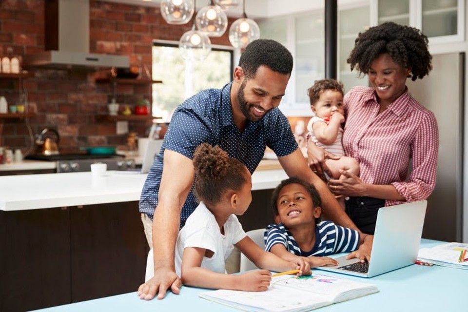 Smiling parents help their young children with homework at the kitchen table.
