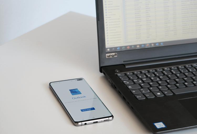 Smartphone mit Outlook-App und Laptop mit Access-Tabelle