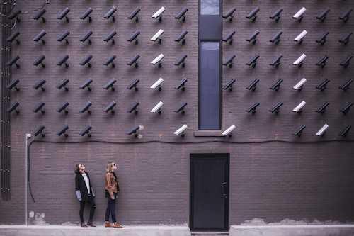 Dos mujeres mirando hacia una pared llena de cámaras de seguridad