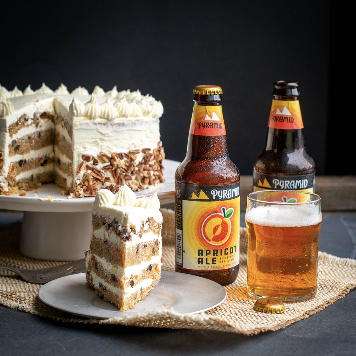 A slice of homemade carrot cake served with a glass of apricot ale, the dessert served in front of the whole carrot cake, tastefully decorated with a cream cheese pineapple frosting, two bottles of pyramid apricot ale linger to the side of the photo paying homage to the cake's signature ingredient - Pyramid Apricot Ale