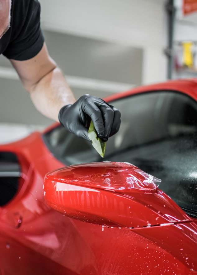 Paint protection film (PPF) being applied to side mirror of red Ferrari 458 GTB