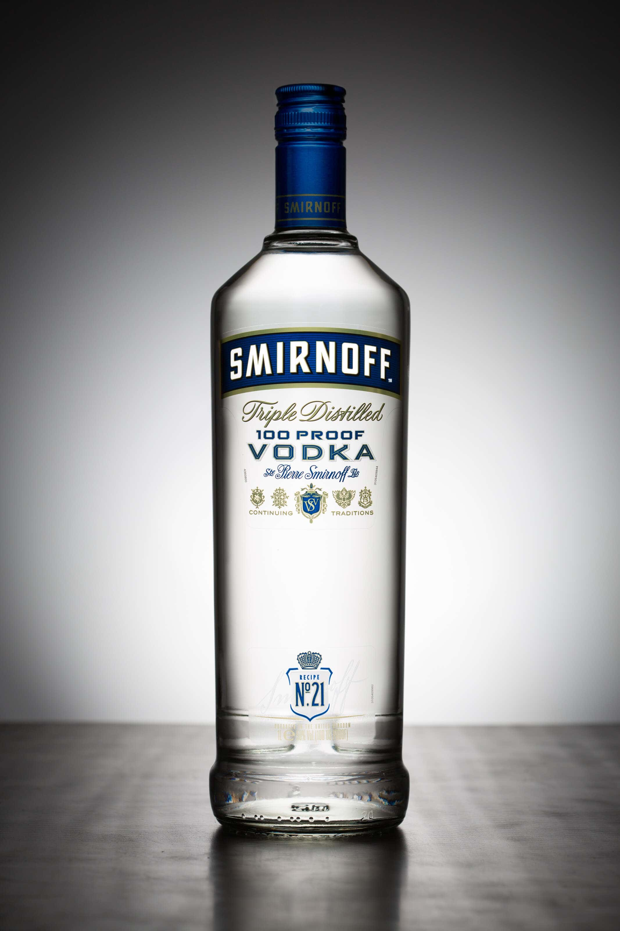 Smirnoff bottle image shot sitting on brushed stainless steel with a white halo behind.