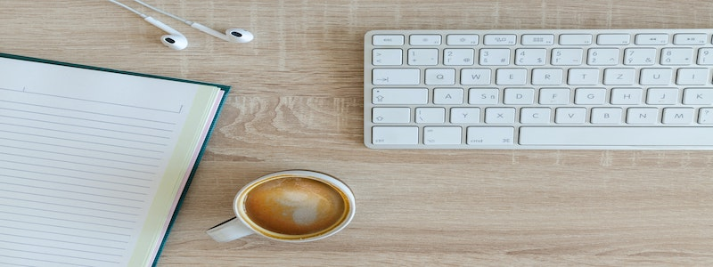 A cup of coffee, notebook, and keyboard on the table