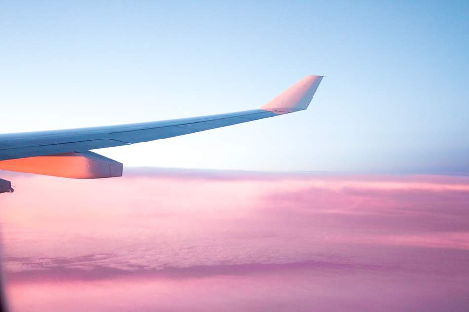 An image of a plane wing above the clouds at sunset