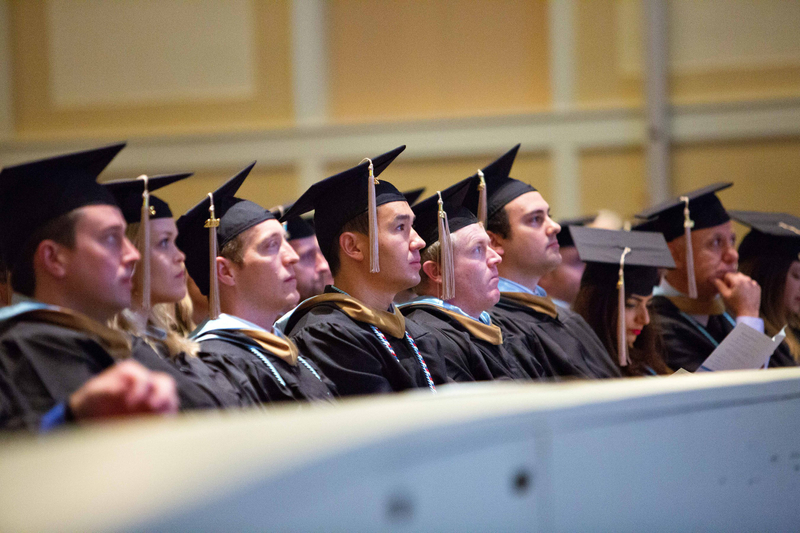 College graduates look on as their graduation ceremony commences