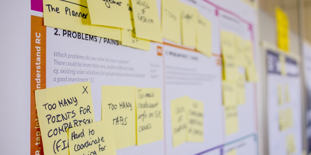 Sticky notes all over a customer journey map on a wall, detailing user pain points