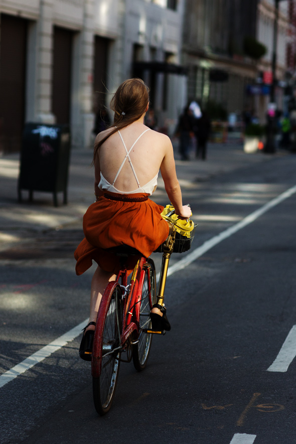 A woman riding a bicycle on the streets of New York City. The Sartorialist, a street fashion photographer, snaps her from behind, and draws attention to her summery, strappy backless dress and flowing hair.