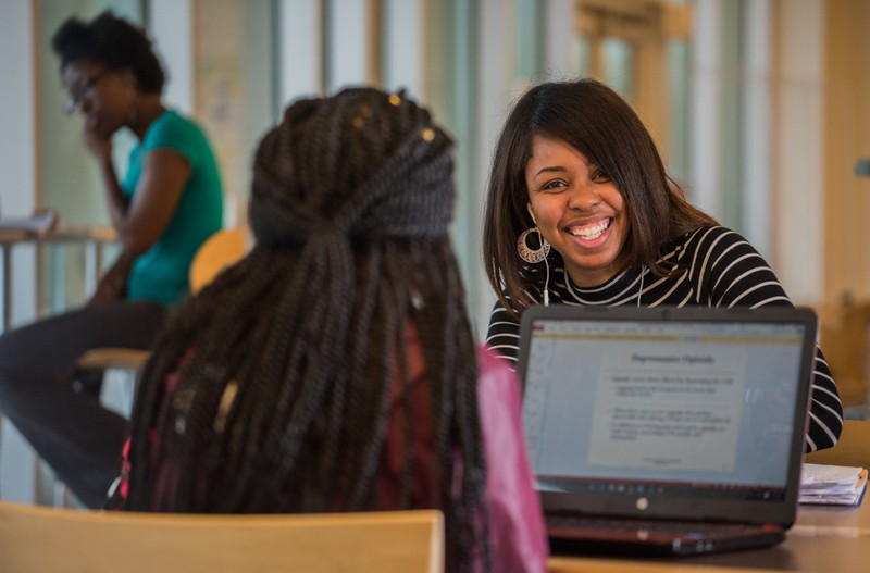 Norfolk State University students smiling working together on their laptops