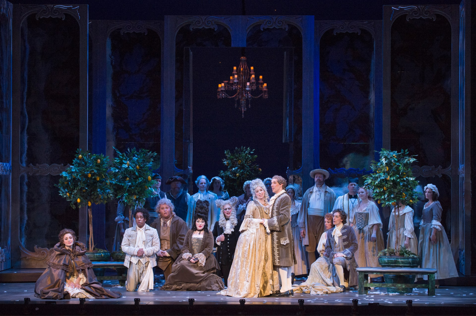 Opera players in elaborate 18th century attire sing under moonlight in front of topiary, chandelier, and towering revolving doors.
