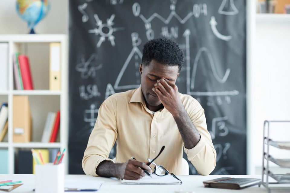 A tired teacher holds a hand to their forehead while sitting at a desk.