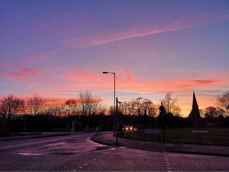 The silhoutte of the trees and Heslington Church are in the foreground, while the background is a deep blue sky and light pink clouds, just before sunset.