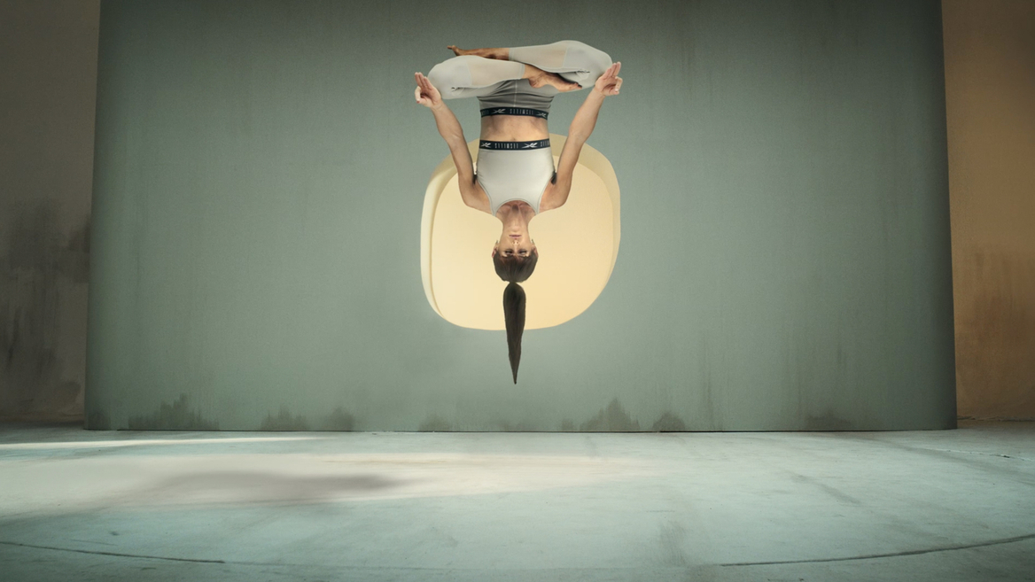 Les Mills Yoga For Now still of woman floating upsidedown