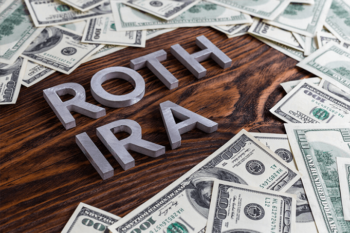 Money scattered around on a table with the words Roth IRA.