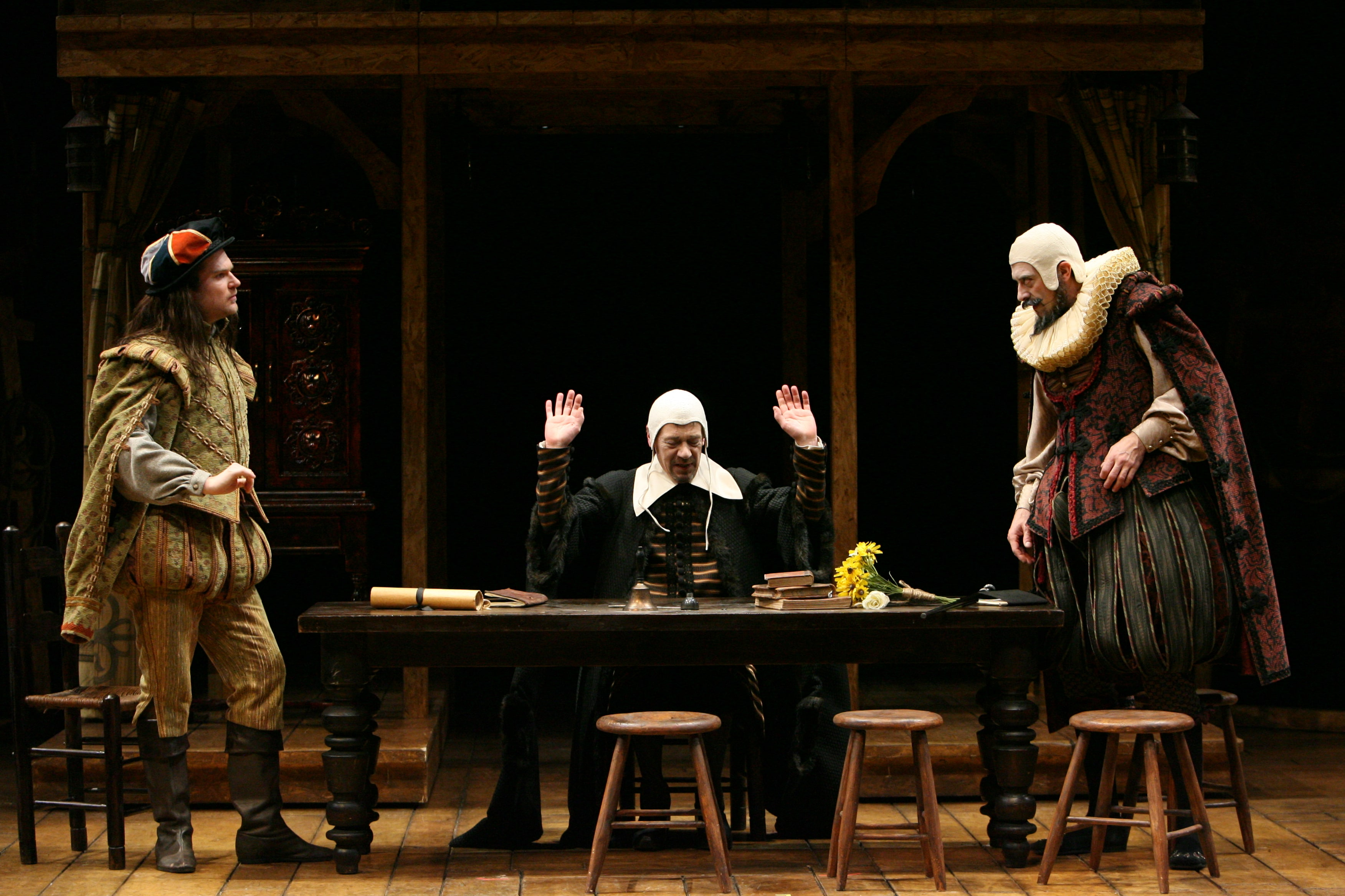 Three men in Elizabethan garb and caps around large wooden table with books on top.
