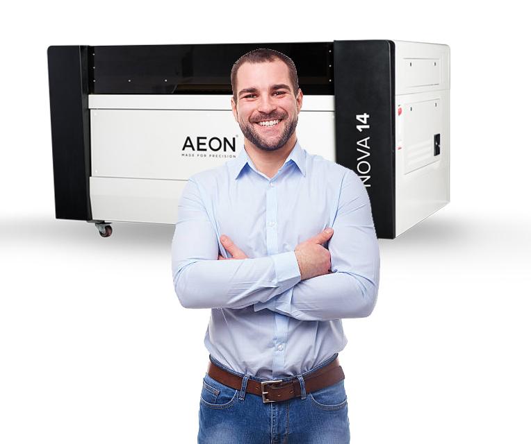 happy dude standing in front of a Aeon Nova laser machine