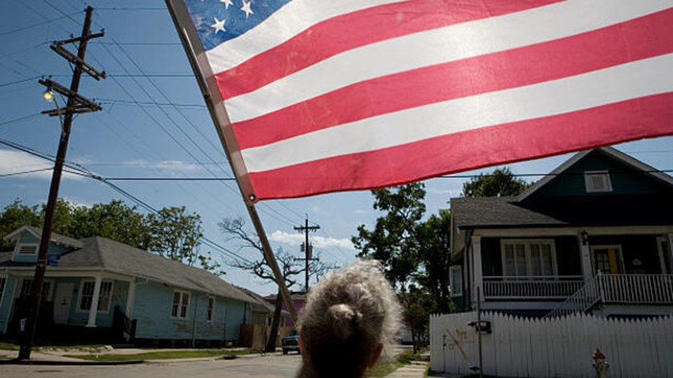 A woman holding a USA flag in a residencial neighborhood