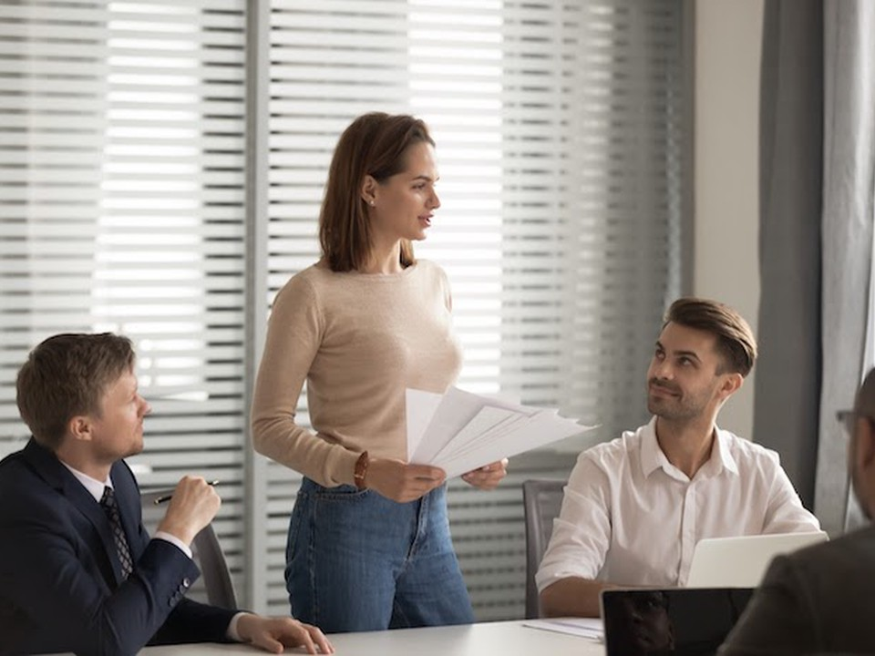 A female education leader mentors three male teachers in a conference room.