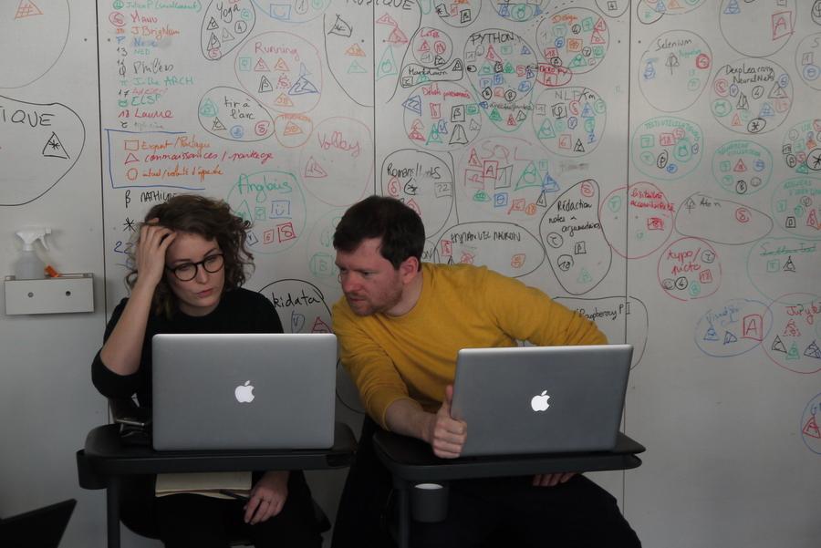 Une femme et un homme travaillent et discutent côte à côte, devant un mur couvert de dessins et de mots.