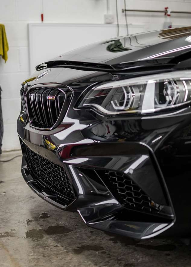 Front of black BMW M2C before paint protection film (PPF)