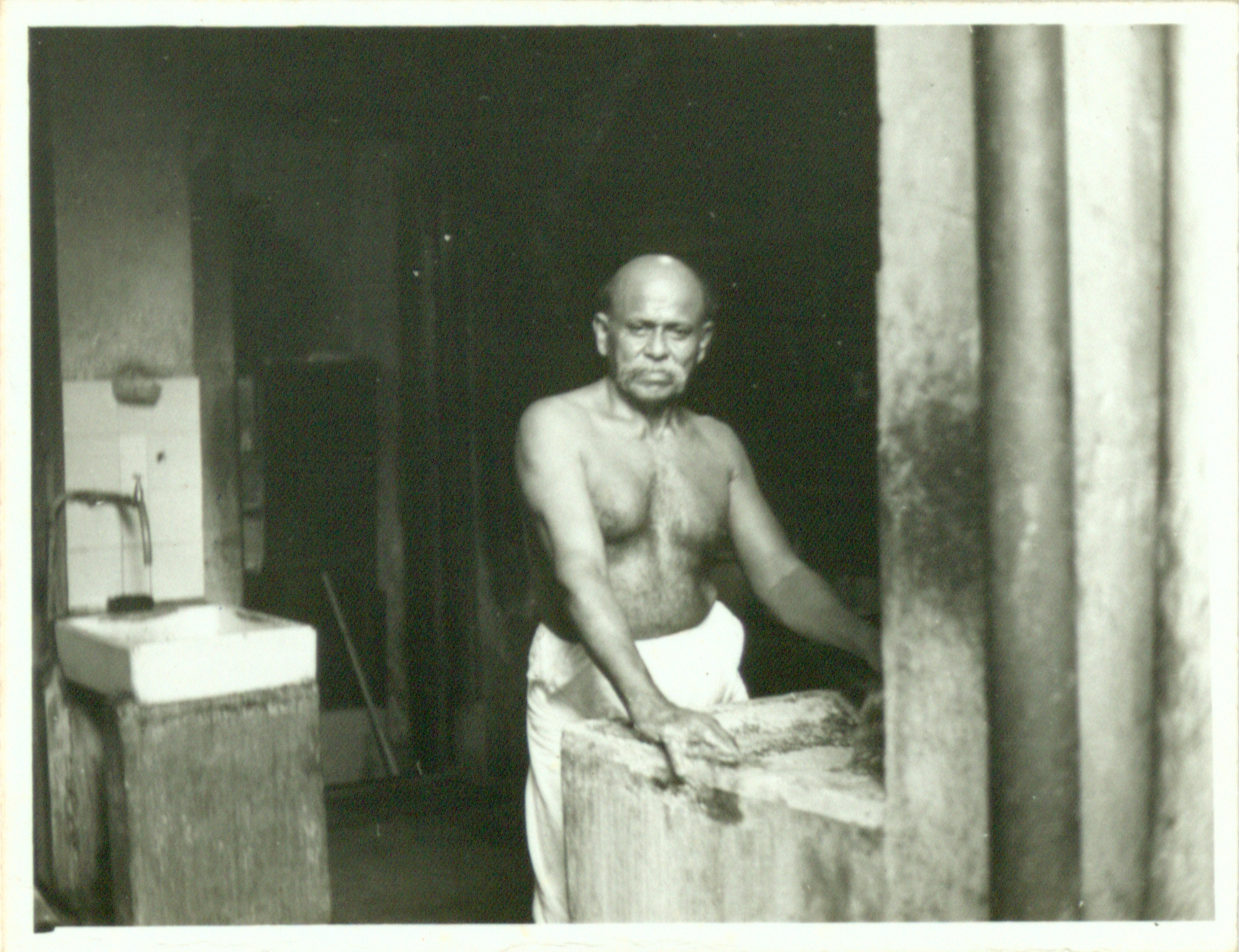 A cook grinding some spices at the cooking area inside the 49 Market Street Kittengi, 1970. Nachiappa Chettiar Collection, courtesy of National Archives of Singapore