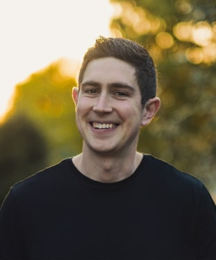 Portrait image of Peter Mazzioli, account manager for Wunder Rent. Short black hair, glowing smile, standing in front of a natural golden sunset.